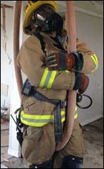 Firefighter hanging on hose ready to be pulled up