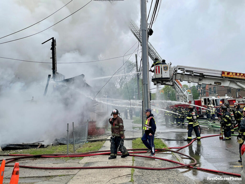 Firefighters put multiple hose streams on the fire, including firefighters flowing water from the bucket of a tower ladder
