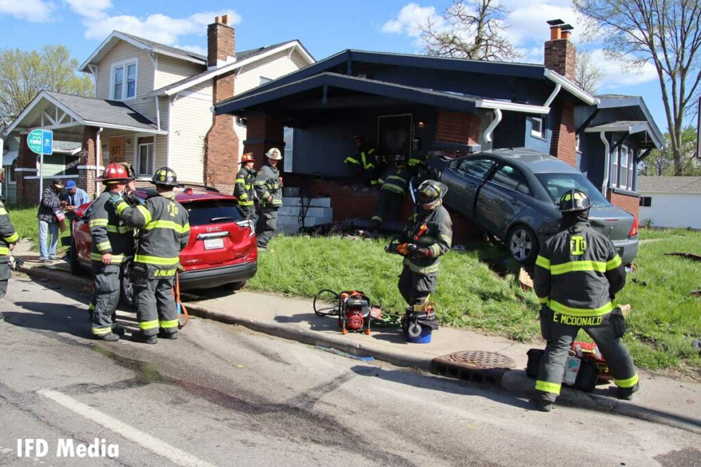 Firefighters at the scene of a crash that sent one vehicle into a porch
