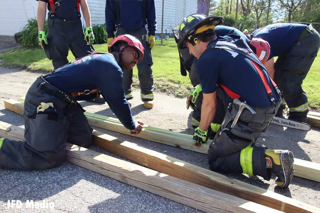 Firefighters consult while constructing a shoring mechanism