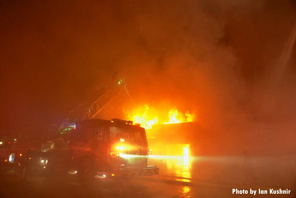 A fire truck illuminated by flames in the background with an aerial master stream at work