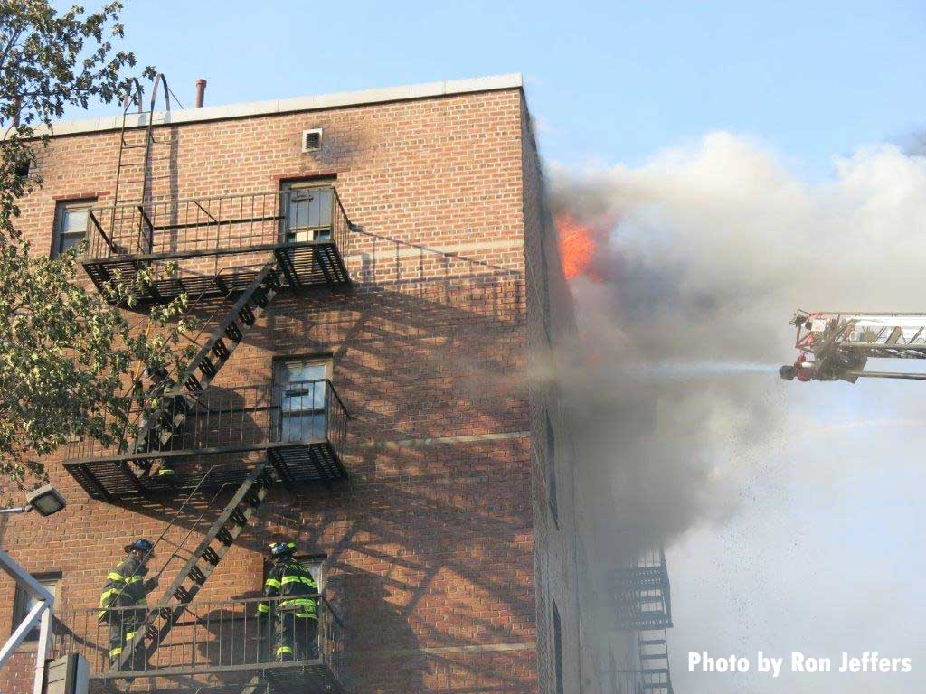 Firefighters on fire escape as aerial puts water on flames at apartment fire