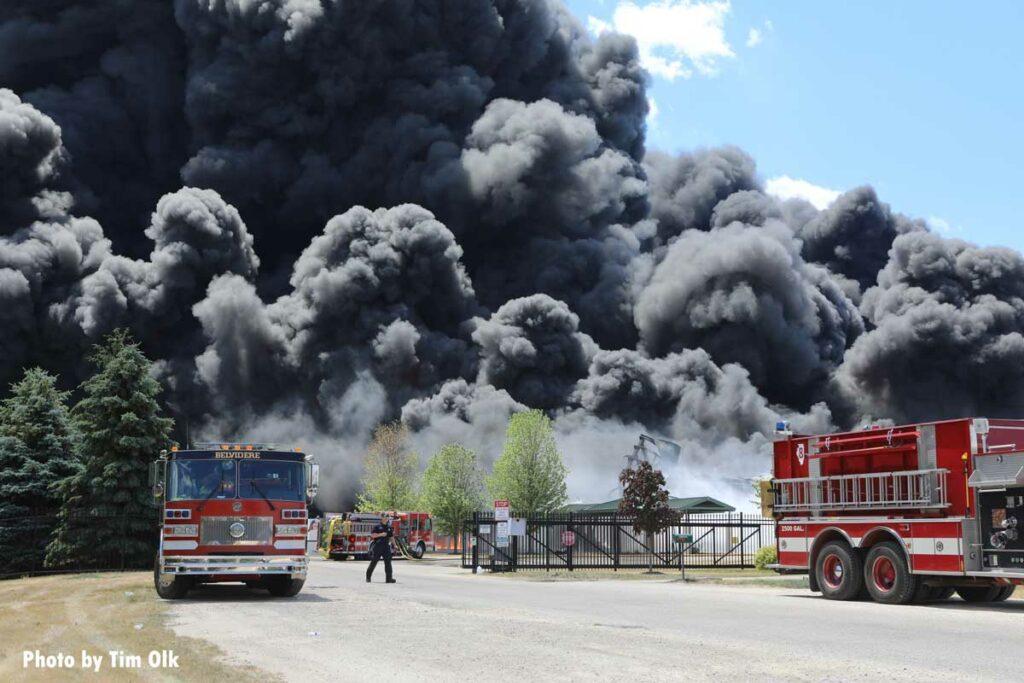 Huge plumes of black smoke drift past multiple fire apparatus