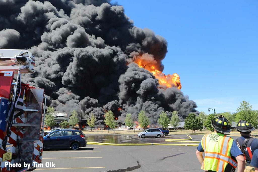 Huge flames and smoke shoot into the sky with firefighters in the foreground