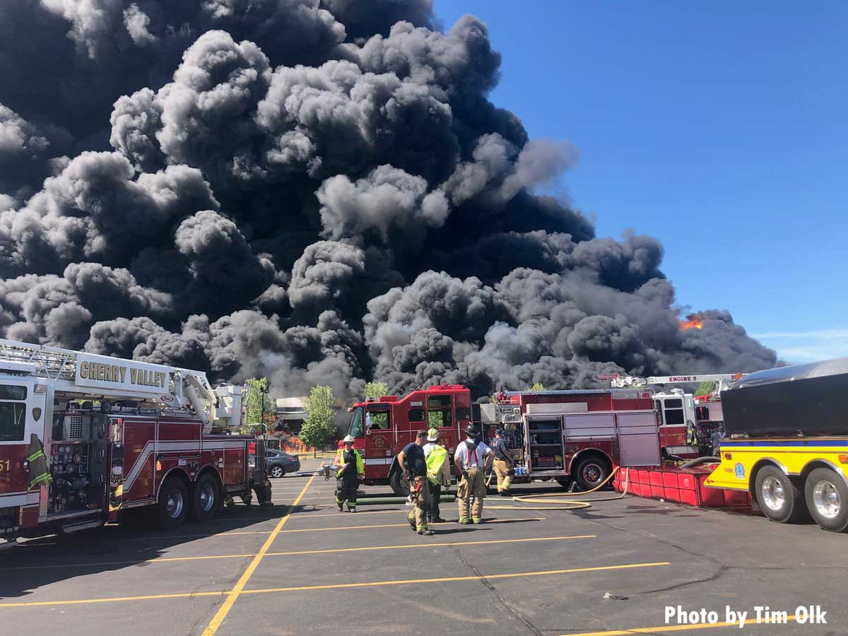 Giant plumes of smoke show the scale of the incident with fire trucks in foreground
