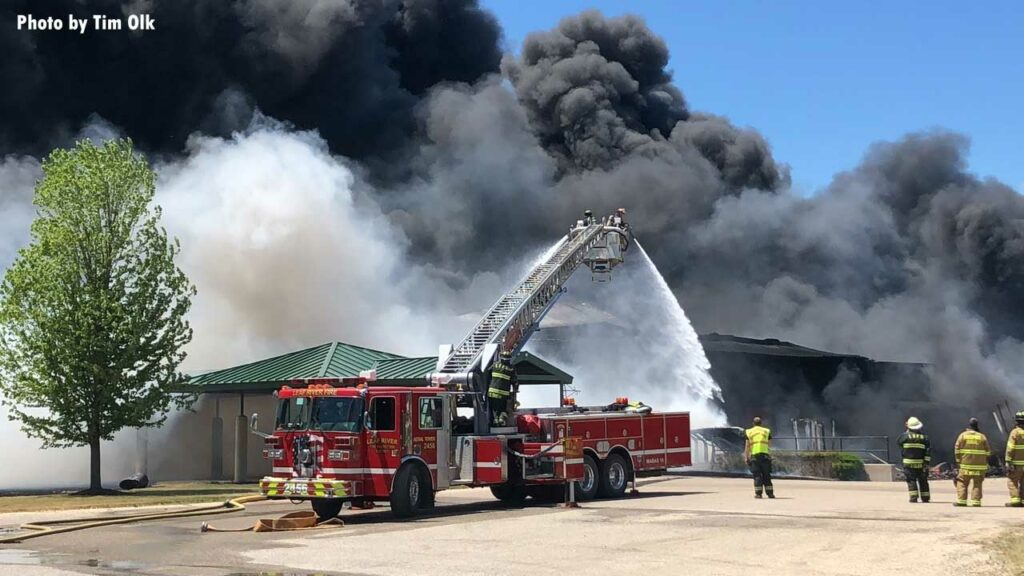 Tower ladder flows water on burning building as black smoke rears up