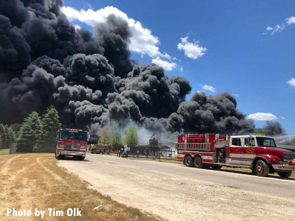 Gigantic plumes of smoke drift through sky past fire trucks