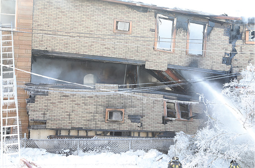 A view from the B side of the structure shows the building's overall instability while the fire continues to burn.