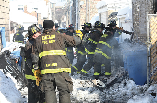 Firefighters work in snow conditions to bring the fire under control.