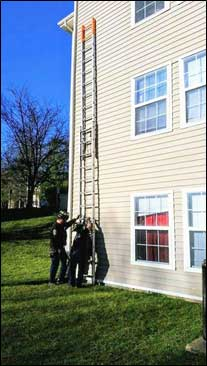 Staged photo of two firefighters butting a ladder against a building