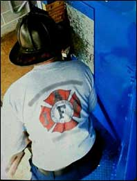 Staged photo of firefighter using a halligan and wedge, forcing the door solo.