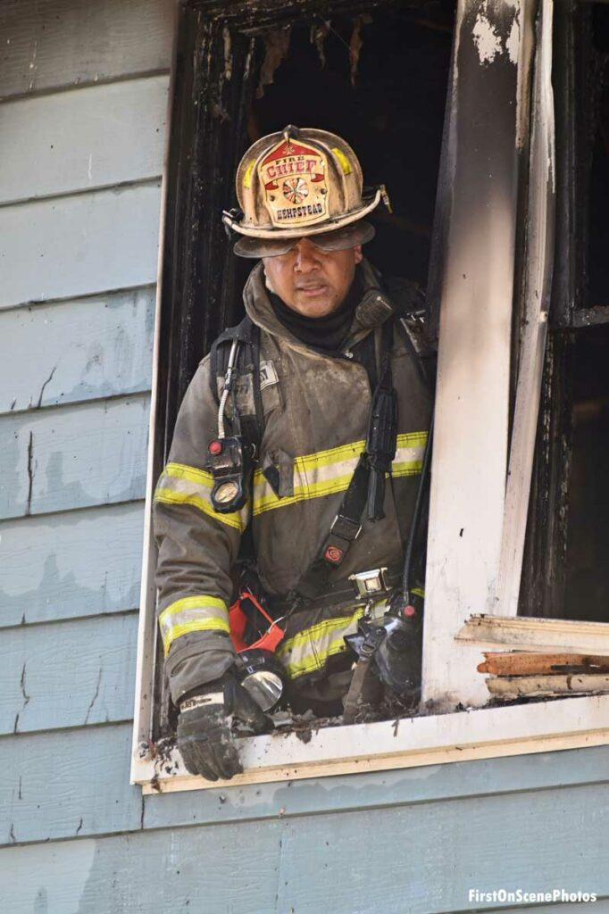 Fire chief leans out charred window at house fire in Hempstead, New York