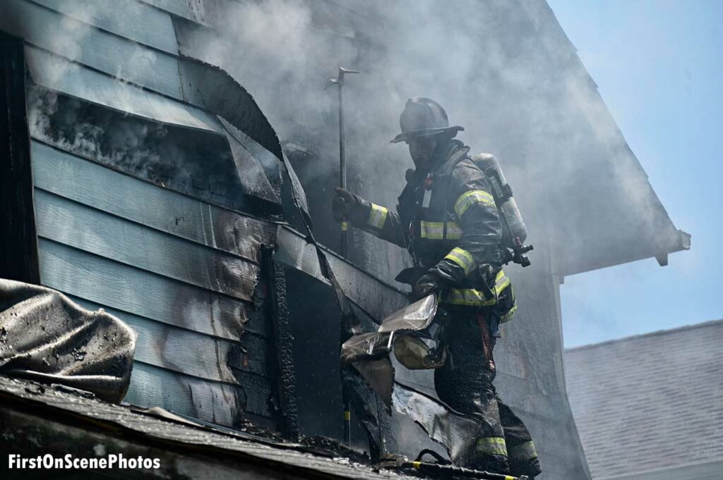 Firefighter performs overhaul on exterior of home amid smoke