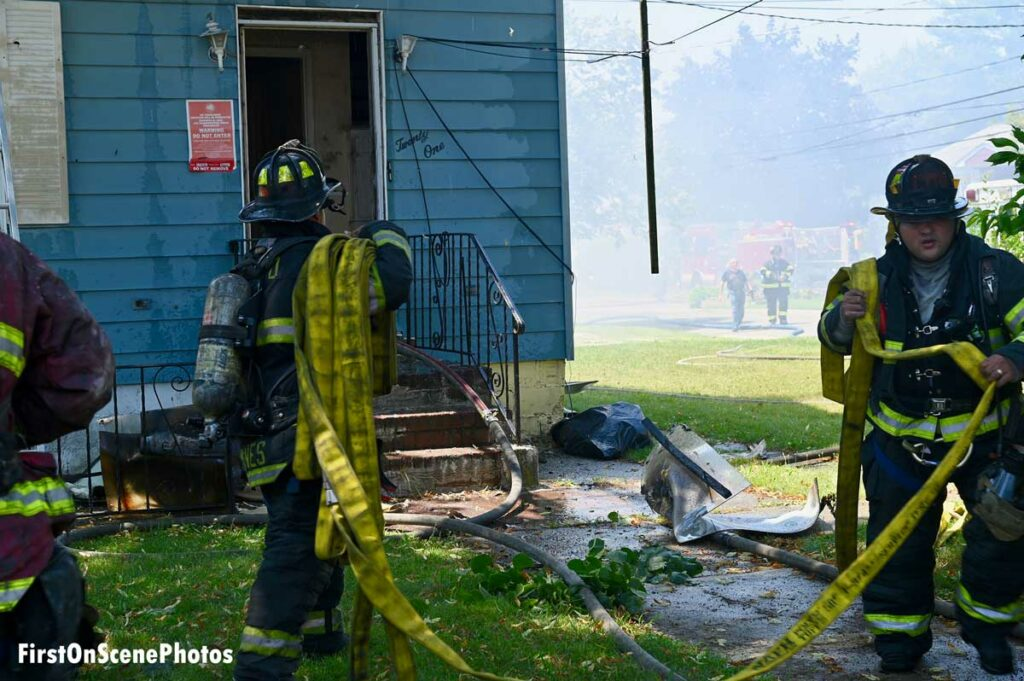 Two firefighters carrying hoselines at house fire
