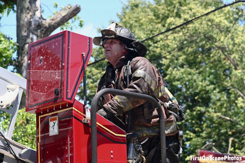 Firefighter operating aerial ladder at fire