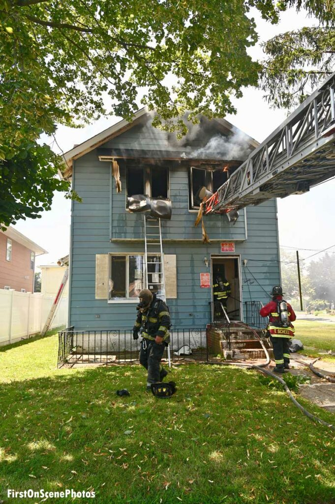 Firefighters, portable ladder, and aerial ladder at scene of Hempstead house fire