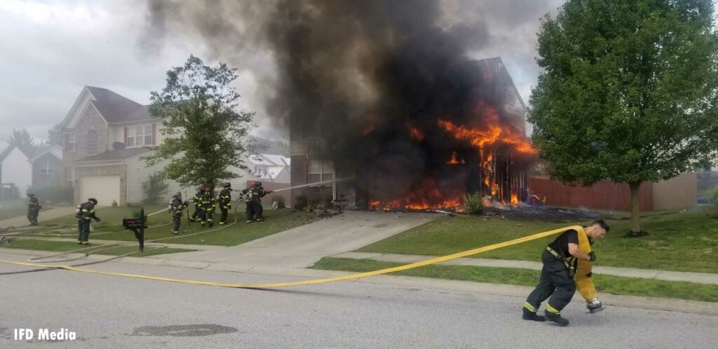 A firefighter drags a supply line at a house fire