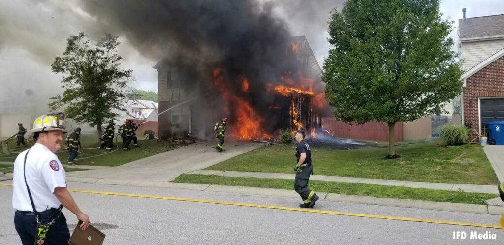 Firefighters put water on a burning home with roaring flames in Indianapolis, Indiana