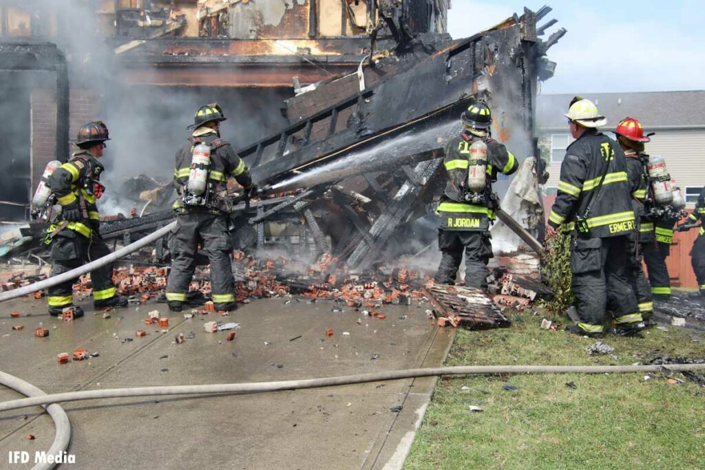Firefighters put water on a charred, collapsed garage