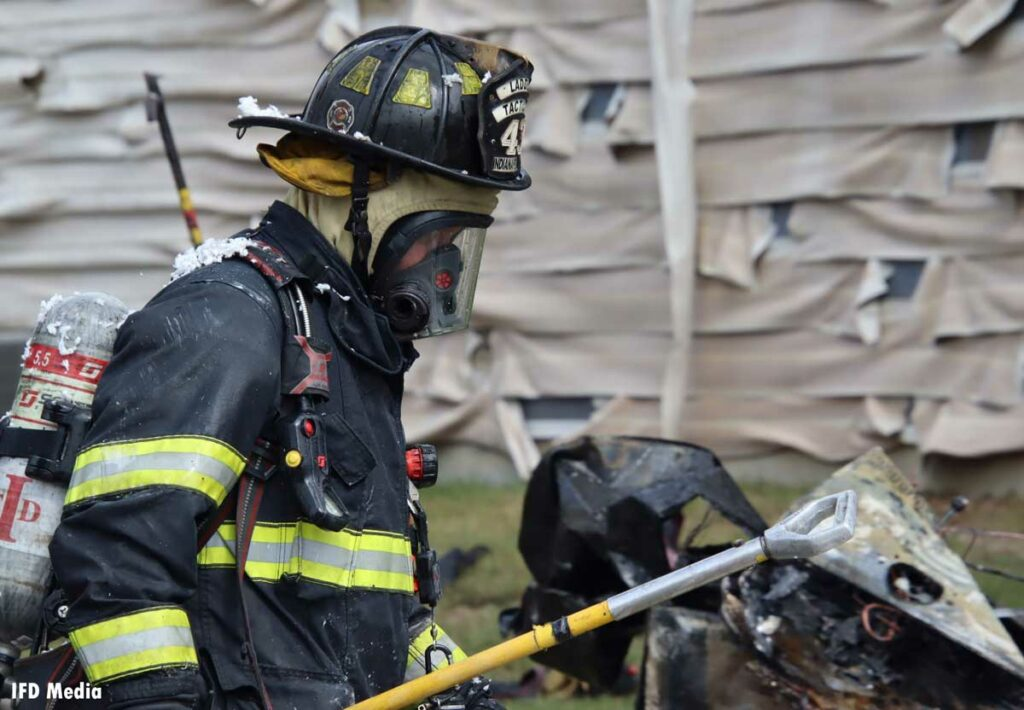 A firefighter in full gear and SCBA with a hook