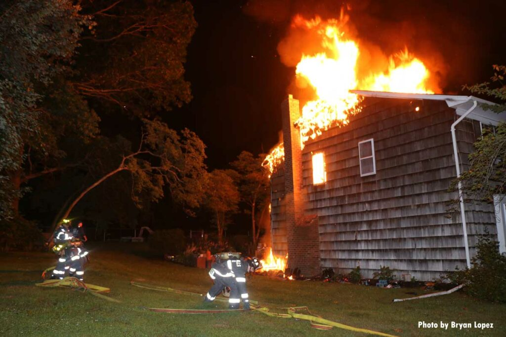 Firefighters flake out a hoseline at a burning home on Long Island