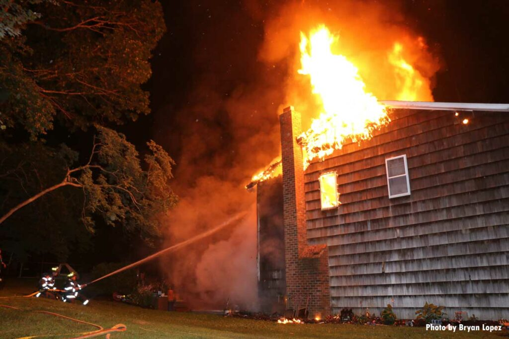 Firefighters train a hoseline on the burning exterior of a Long Island home
