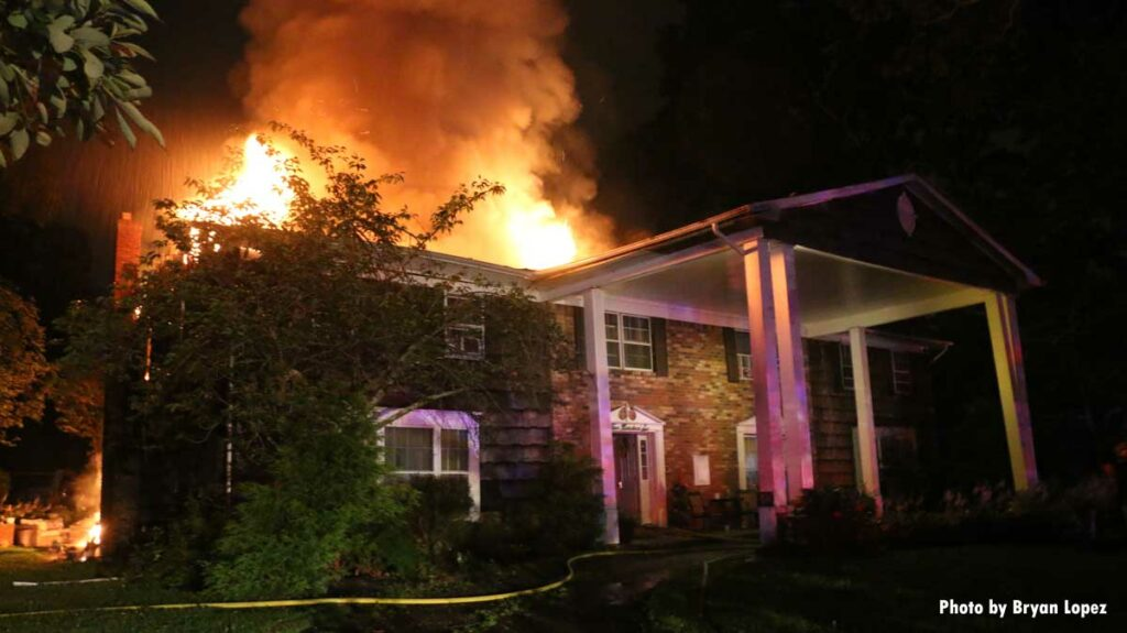 Flames pour from the roof of a Long Island home