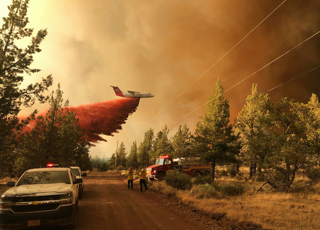 Plane drops fire retardant on wildfires in West