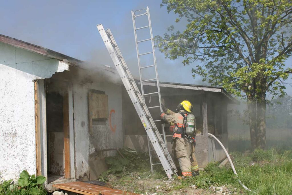 Firefighter with multiple portable ladders at house fire