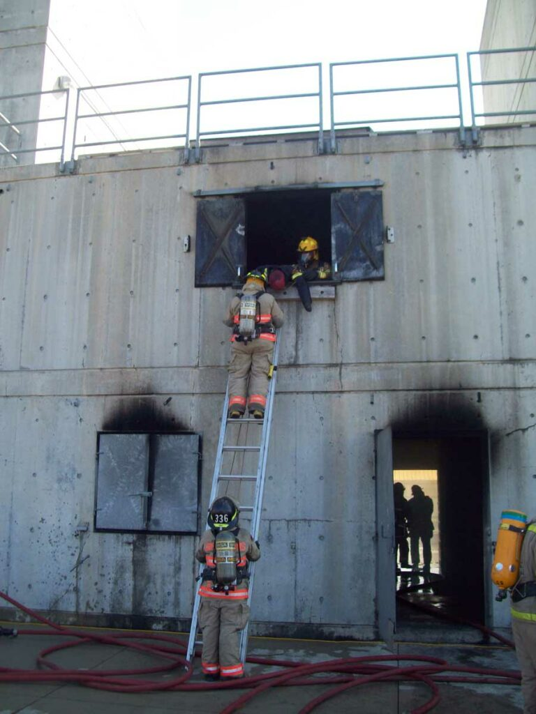 Firefighter footing the ladder at burn building