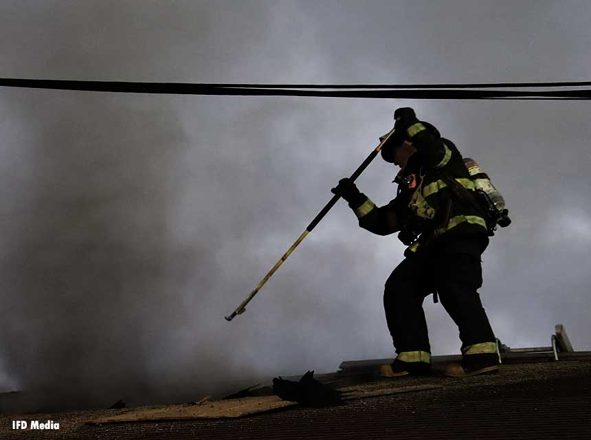 Indianapolis firefighter on roof with a hook