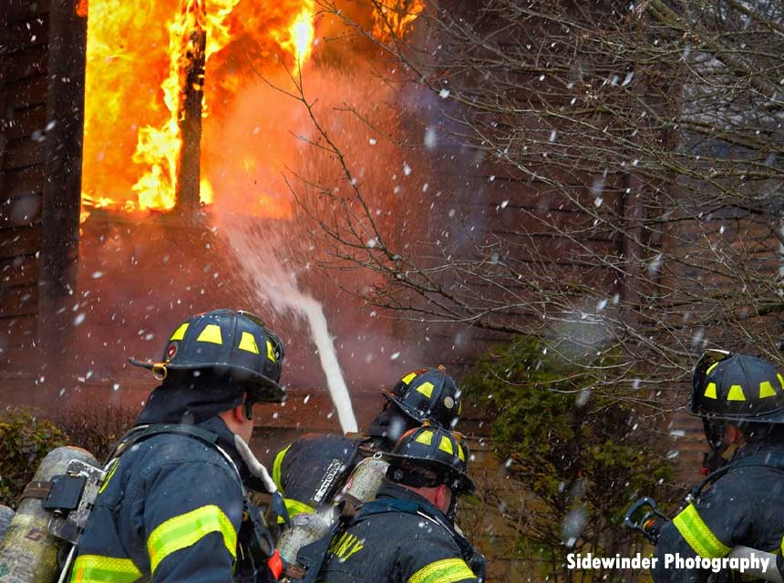 Firefighters operate a fire blowing out a window in Albany, New York