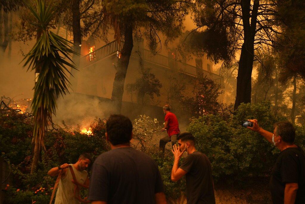 Flames burn a home at Pefki village on Evia Island in Greece