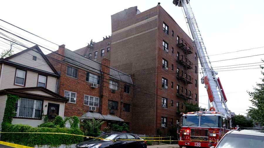 Firefighters are seen on the rooftop of a building on 43rd Ave. in Queens after an explosion.
