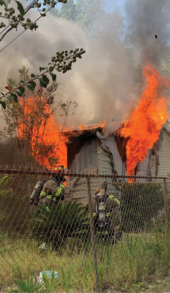 firefighters with flames blowing out of home