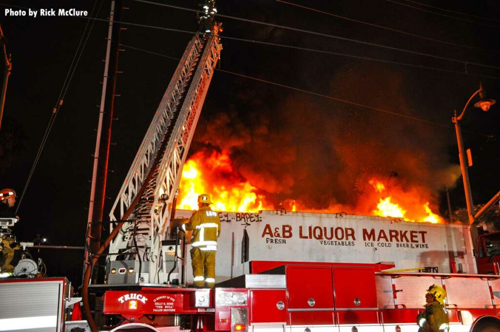 LAFD Truck 2 with aerial ladder extended as flames shoot from building
