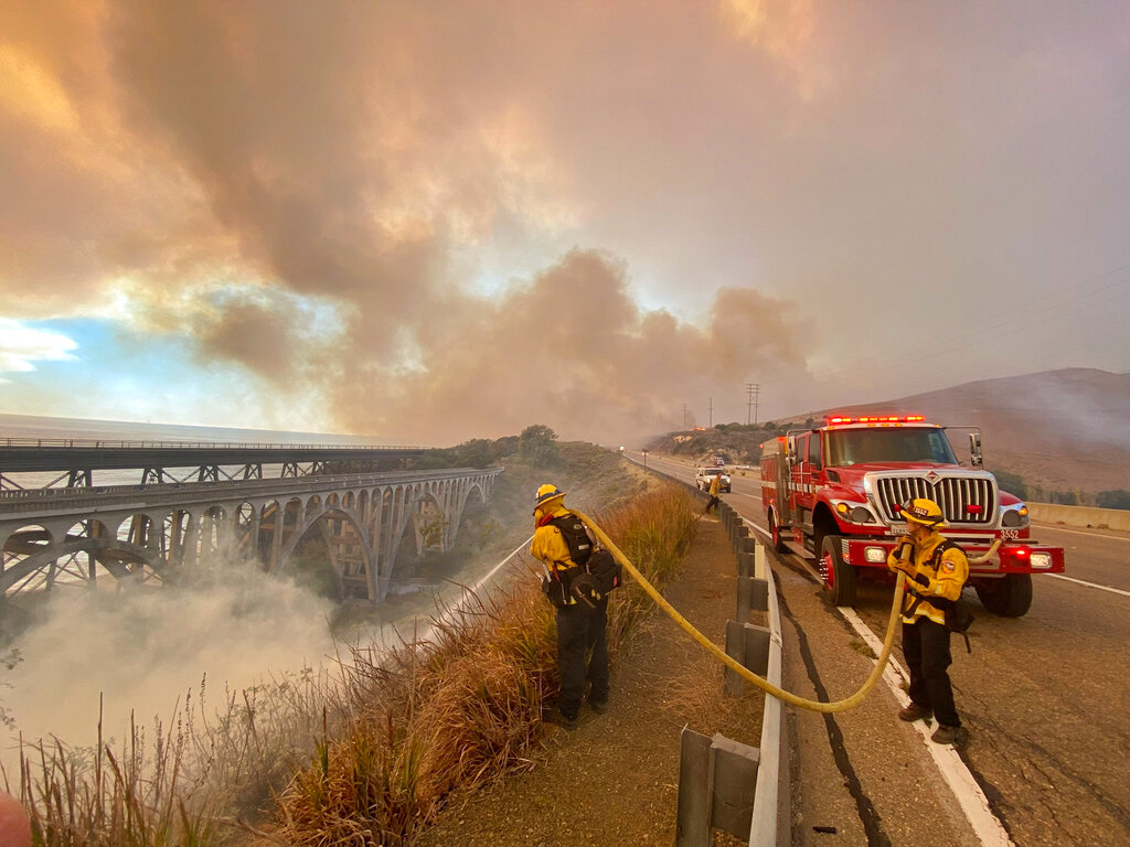 Firefighters extinguish flames near California highway