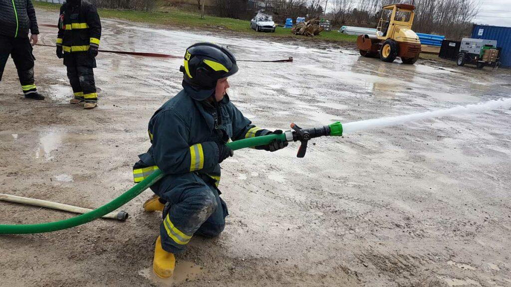 Firefighter in Euro helmet flowing water