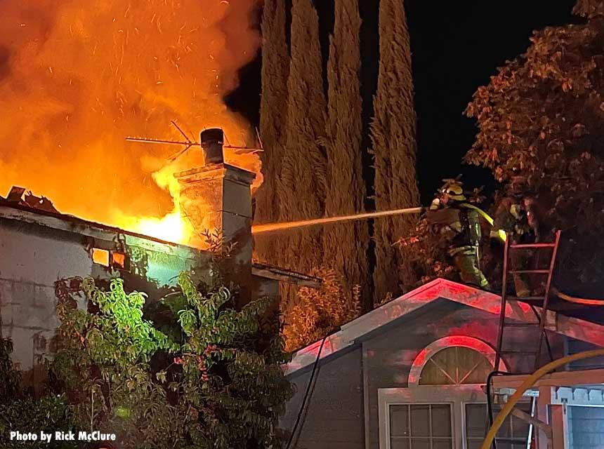 A firefighter applies an exterior stream at a structure fire